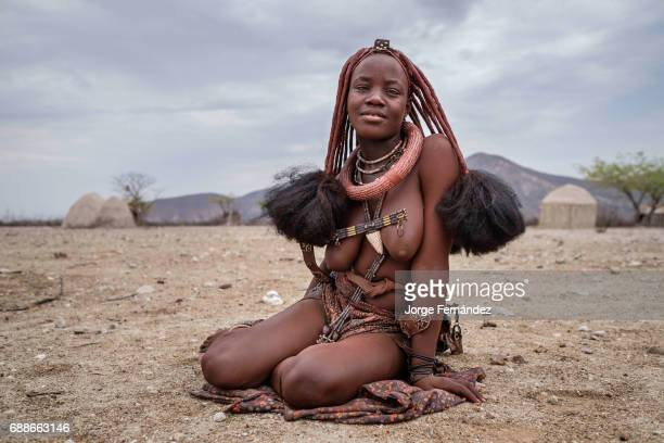 Portrait of a Himba woman sitting on the ground in a small village Himbas are a bantu tribe who migrated into what today is Namibia a few centuries...