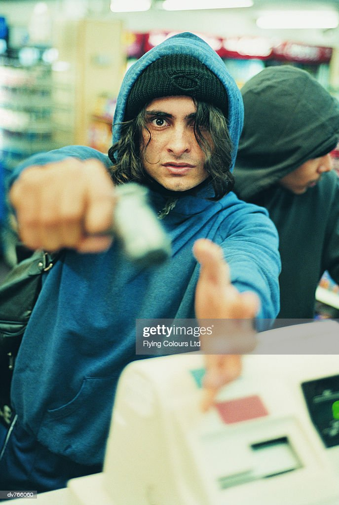 Portrait of a Hooded Robber With Another Man Aiming a Pistol : Stock Photo