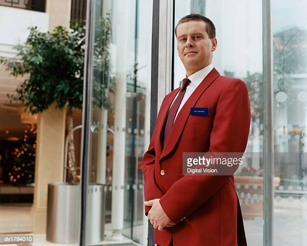 Portrait of a Hotel Doorman in a Smart Red Jacket, Standing in a Lobby by the Entrance