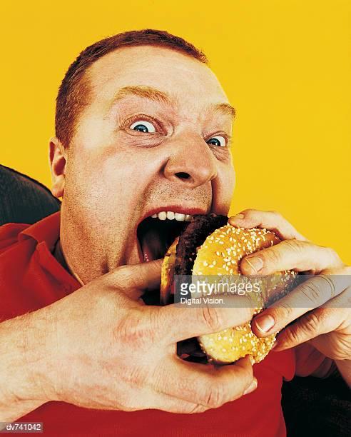 Portrait of a Hungry Man Eating a Hamburger