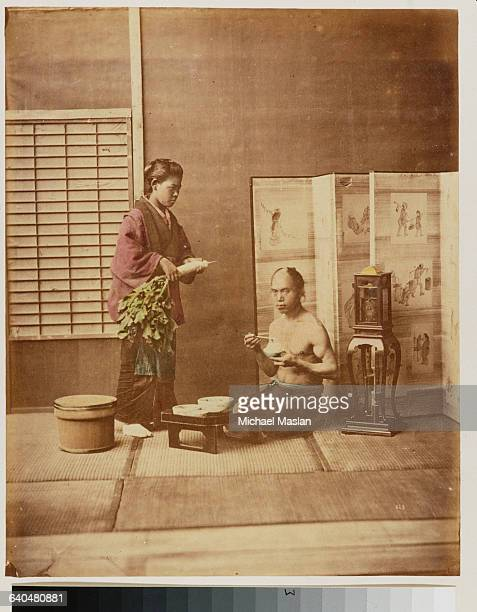 A portrait of a Japanese man and woman in regional attire in a domestic scene The man eats rice with chopsticks while the woman holds a daikon Japan...