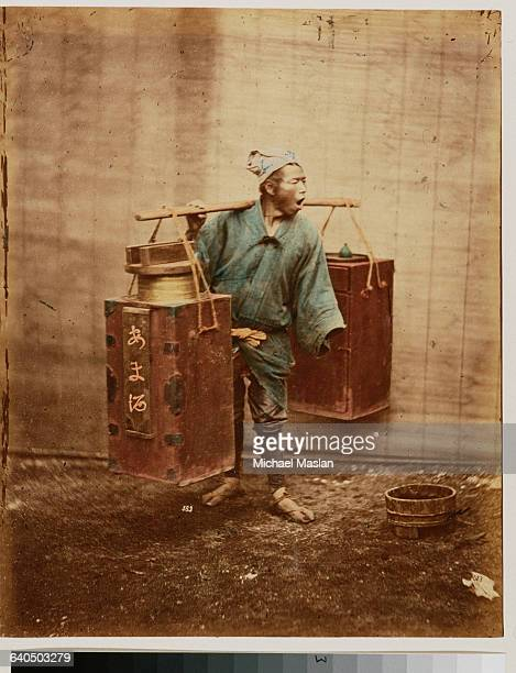 A portrait of a Japanese merchant or porter carrying two large metal cannisters by hanging them from the two ends of a wooden pole and balancing the...