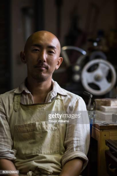 Portrait of a jewellery artist in his metal working workshop