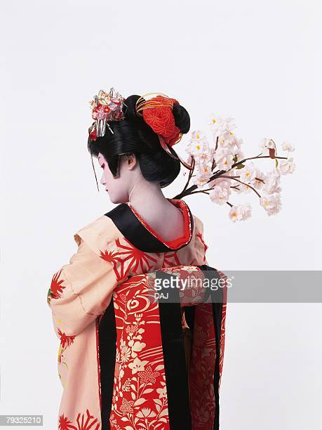 Portrait of a Kabuki actor acting as female with a branch of cherry blossoms, Rear View