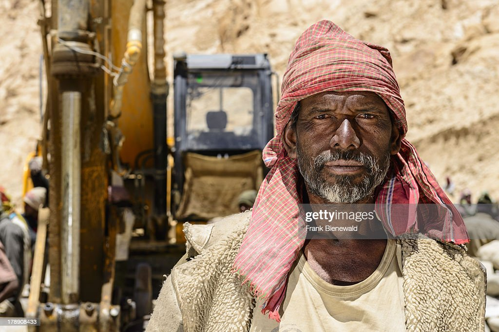 LADAKH CHUMATANG JAMMU KASHMIR INDIA A portrait of a labour in front of an excavator who lives in Jharkhand originally but has to work under very...