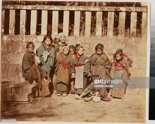 A portrait of a large group of Japanese children of varying ages One woman whose relationship to the children is uncertain can be seen in the far...