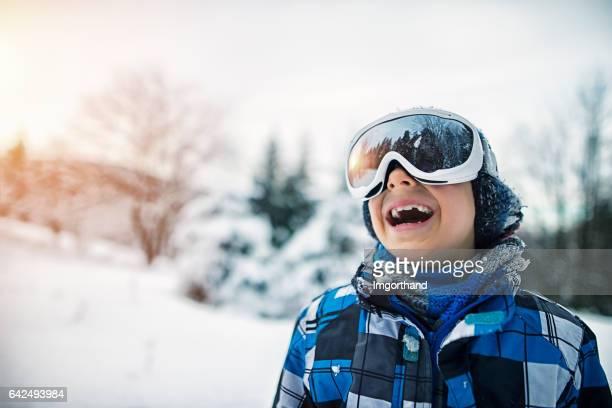Portrait of a little boy skiing in forest