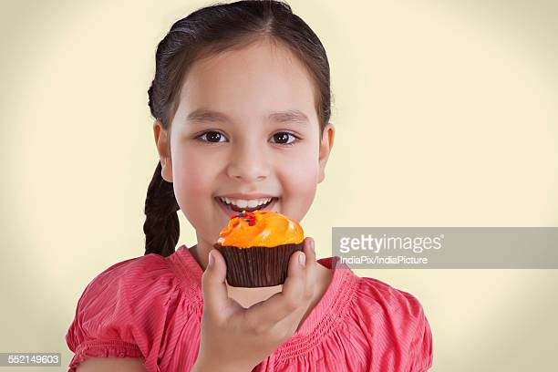 Portrait of a little girl eating a cupcake
