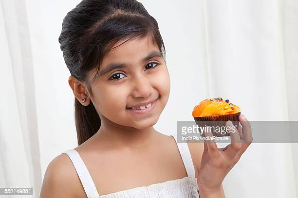 Portrait of a little girl holding a cupcake