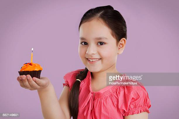 Portrait of a little girl holding a cupcake with a candle