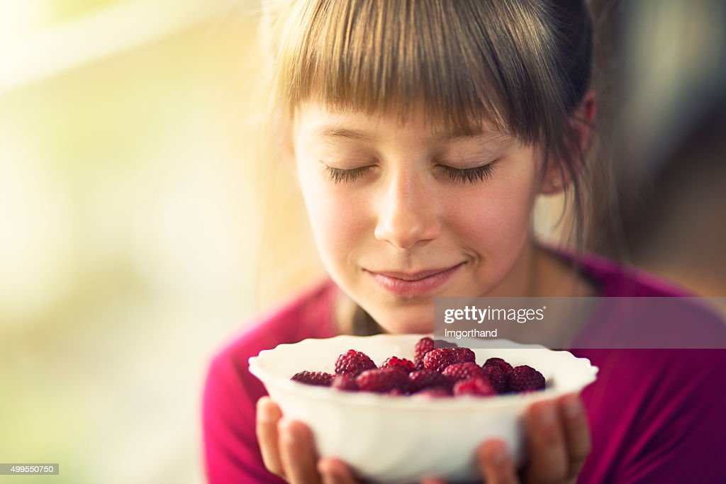 Portrait of a little girl with raspberries. : Stock Photo