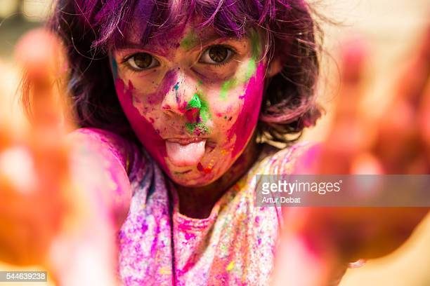 Portrait of a little girl with tongue out showing his hands covered with colorful Gulal powder during a Holi party to give welcome to the springtime during a sunday family reunion.