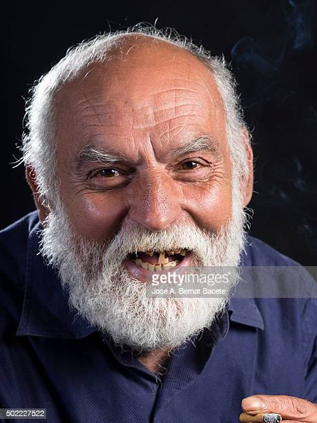 Portrait of a major man of white beard laughing with the mouth opened without teeth, smoking a cigarette.