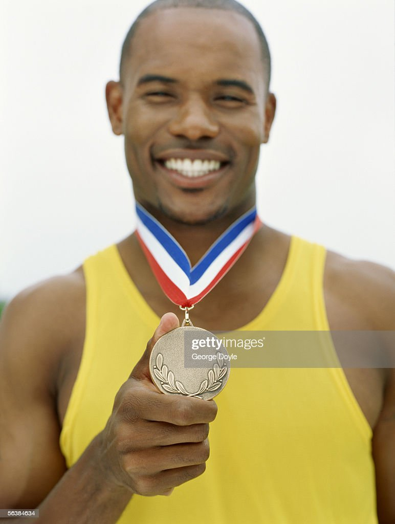 portrait of a male athlete holding his medal