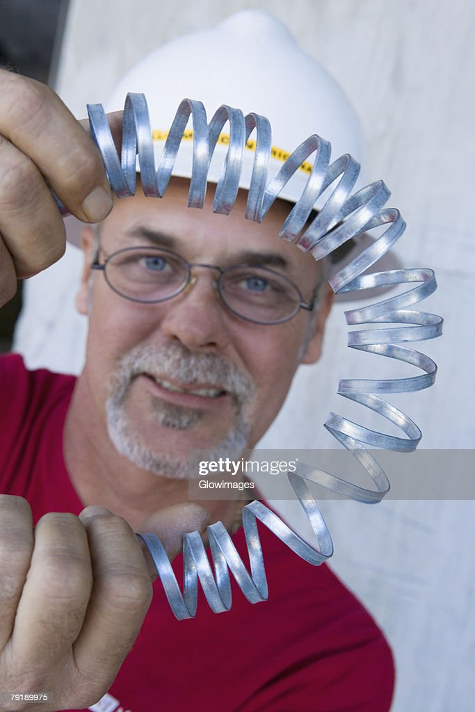 Portrait of a male construction worker folding a metal spring and smiling : Stock Photo
