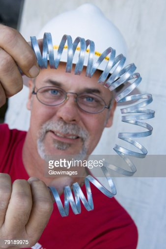 Portrait of a male construction worker folding a metal spring and smiling : Foto de stock