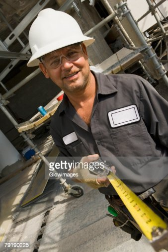 Portrait of a male construction worker holding a tape measure and smiling : Foto de stock