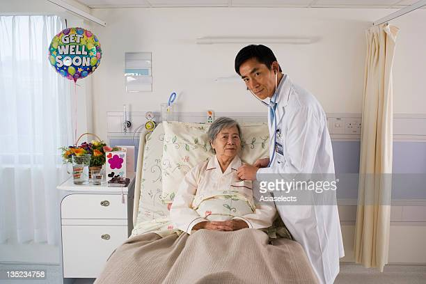 Portrait of a male doctor examining a female patient