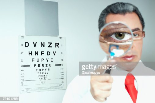 Portrait of a male doctor holding a magnifying glass in front of his eye : Stock Photo