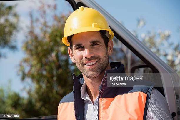 Portrait of a male engineer standing by van at site