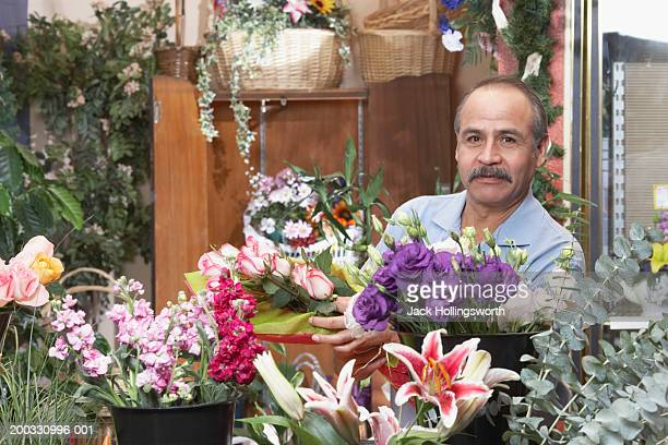 Portrait of a male florist holding a bunch of pink roses in a flower shop