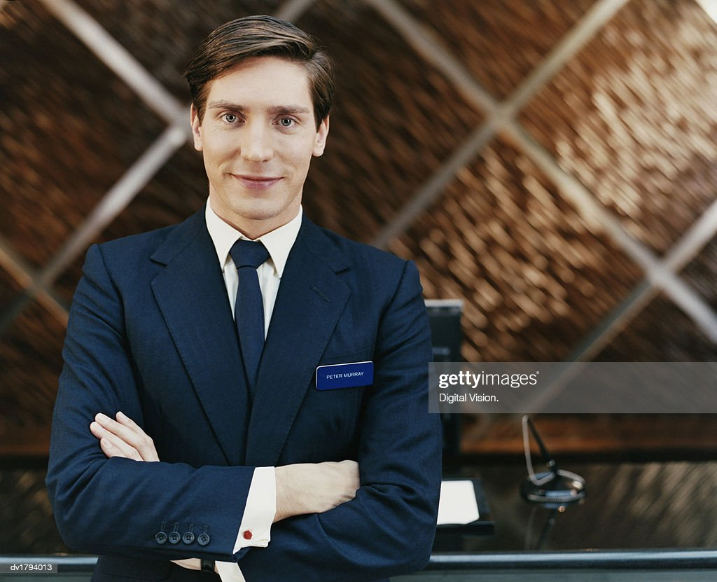 Portrait of a Male Hotel Manager Standing by a Reception Desk : Stock Photo