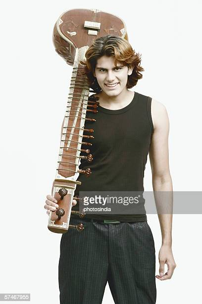 Portrait of a male musician holding a sitar