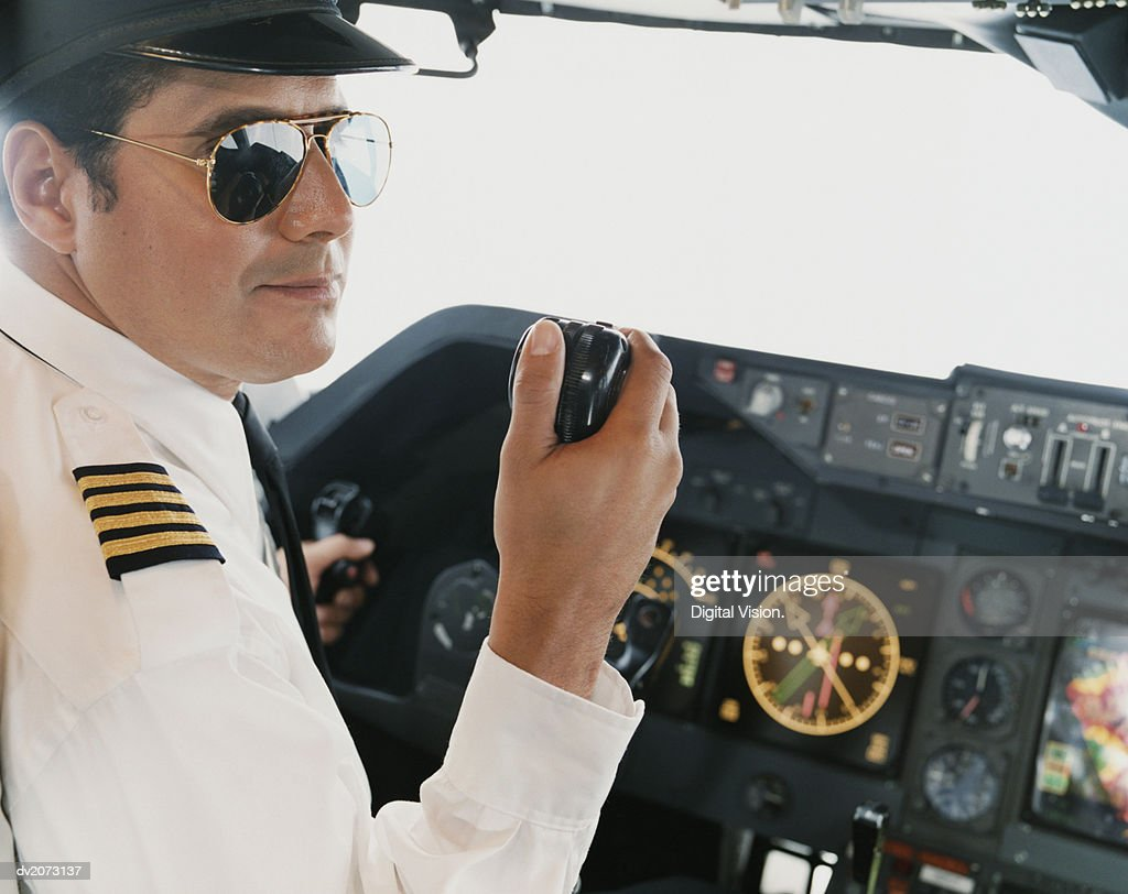 Portrait of a Male Pilot Sitting in the Cockpit Holding a Radio : Stock Photo