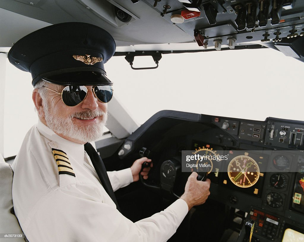 Portrait of a Male Pilot Sitting in the Cockpit : Stock Photo