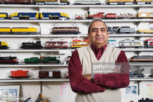 Portrait of a male sales clerk standing with his arms crossed in a toy store