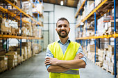 Portrait of a male warehouse worker, arms crossed.