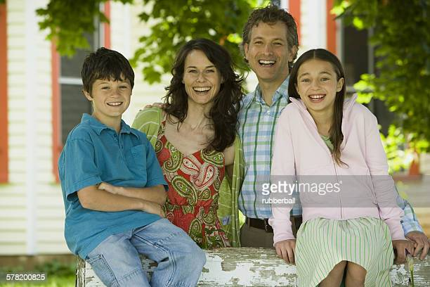 Portrait of a man and a mid adult woman smiling with their children