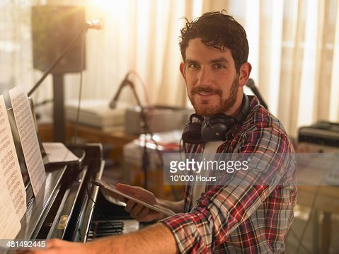 Portrait of a man at a piano holding an iPad