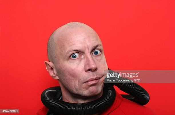 Portrait of a man being sucked by vacuum cleaner .