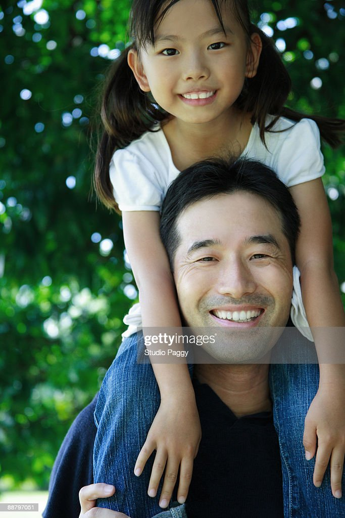 Portrait of a man carrying his daughter on shoulders : Stock Photo