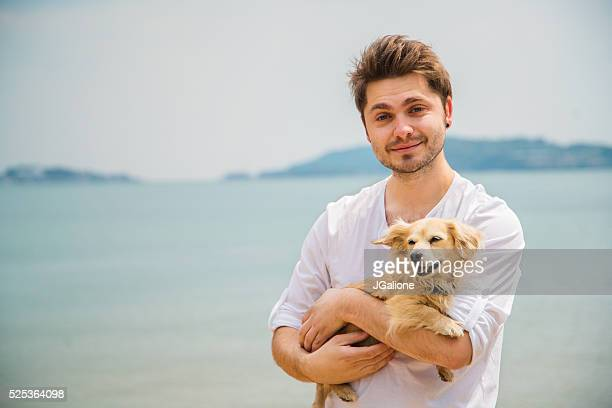 Portrait of a man holding a dog on the beach