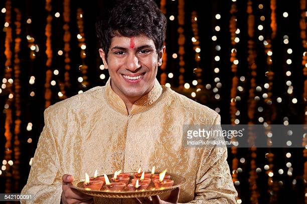 Portrait of a man holding a tray of diyas