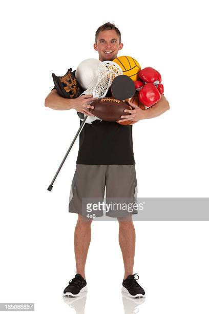 Portrait of a man holding sports equipments
