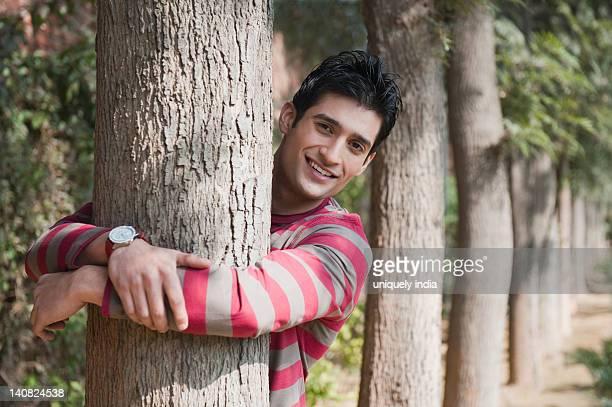 Portrait of a man hugging a tree