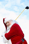 Portrait of a Man in a Father Christmas Costume Swinging a Golf Club