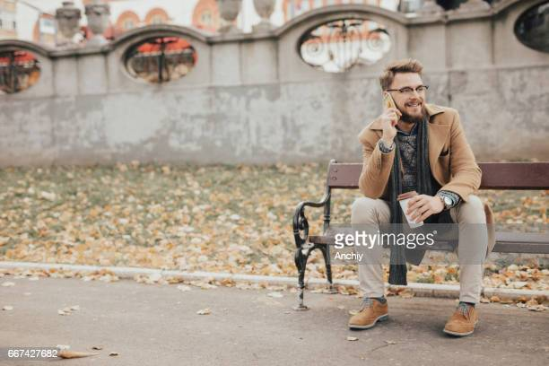 Portrait of a man in warm clothes sitting in the park during autumn