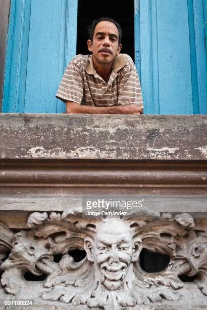 Portrait of a man looking at the camera from his window