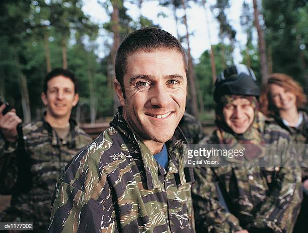 Portrait of a Man Paintballing With Friends Dressed in Camouflage Clothing