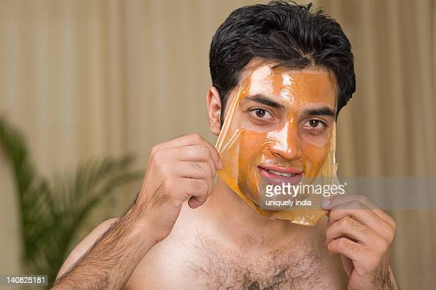Portrait of a man peeling off facial mask from face