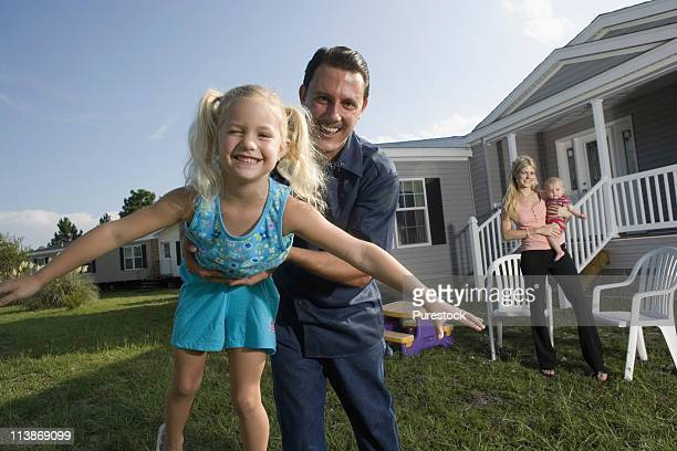 Portrait of a man playing with his family in front of a trailer home