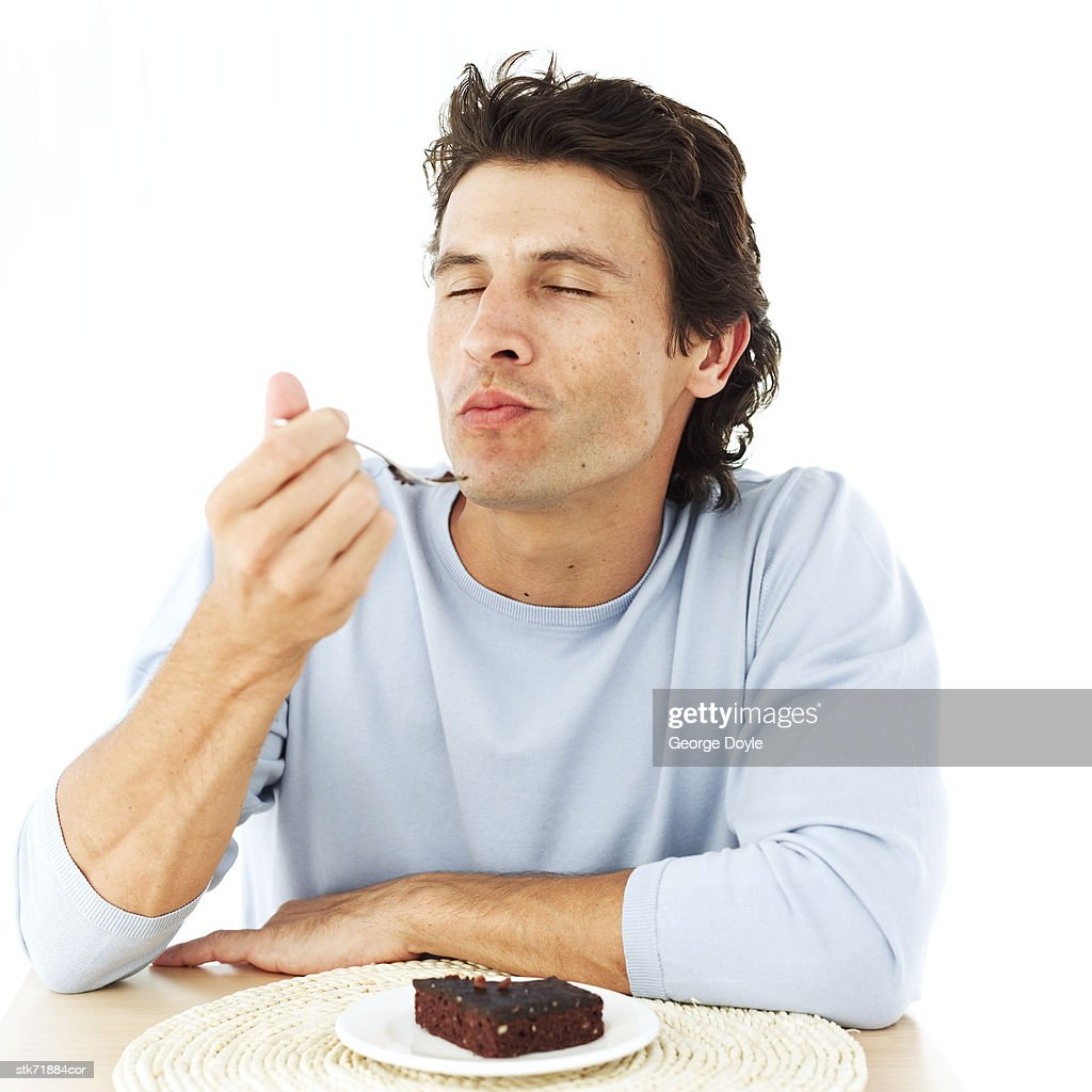 portrait of a man savoring a brownie with his eyes closed : Stock Photo