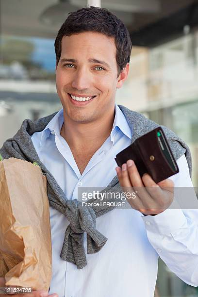 Portrait of a man showing empty wallet with paper bag full of vegetables