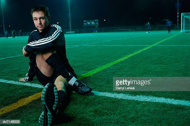 Portrait of a Man Sitting Down at the Edge of a Football Pitch