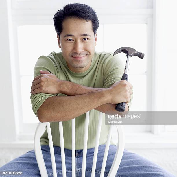 Portrait of a man sitting on a chair holding a hammer