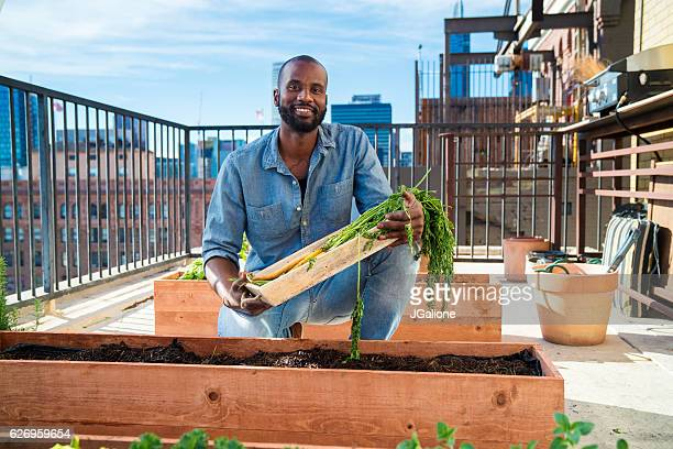 Portrait of a man tending to his rooftop garden